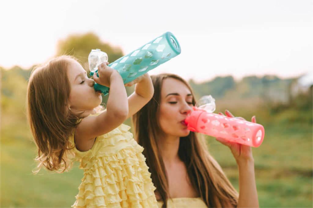 Frau und Kind beim Wasser trinken